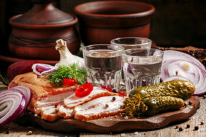 Russian tradition: cold vodka and a snack of bacon, pickles, red